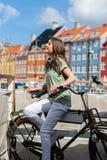 看边的自行车的年轻愉快的妇女 免版税图库摄影