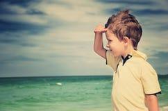 看远离他的在背景的棕榈的被定调子的图象男孩  库存图片