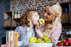 看逗人喜爱的矮小的儿子的愉快的年轻母亲吃苹果 图库摄影