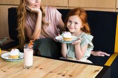 看逗人喜爱的矮小的女儿的微笑的母亲播种的射击拿着板材 免版税库存照片