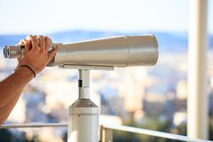 看通过不锈钢双筒望远镜的年轻人  库存照片