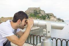 看通过公开双筒望远镜的年轻人在一多云天 免版税库存照片