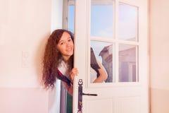 看通过前门的逗人喜爱的十几岁的女孩 库存图片