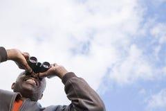 看通过双筒望远镜的一个人 库存照片