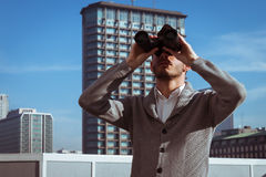 看通过双筒望远镜的一个英俊的年轻人的画象 免版税库存图片