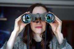 看通过双筒望远镜的女孩的前面画象在窗口里 免版税库存照片