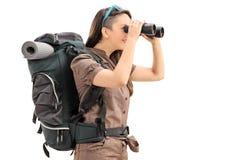 看通过双筒望远镜的女性远足者 图库摄影