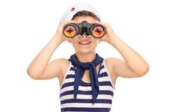 看通过双筒望远镜的小水手男孩隔绝在白色b 库存图片