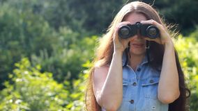 看通过双筒望远镜的少妇游人 旅行在自然未知的地方  股票录像