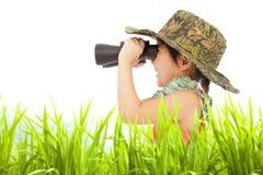 看通过双筒望远镜的愉快的小女孩户外 免版税库存图片