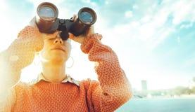 看通过双筒望远镜的美丽的女孩海在一个明亮的晴天 旅行假日旅途概念 库存照片