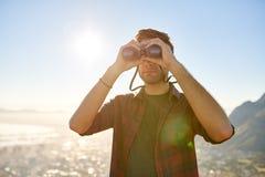 看通过双筒望远镜的年轻人,当户外在太阳火光时 库存照片