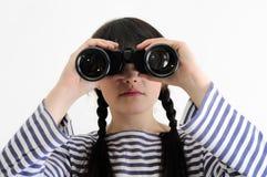 看通过双筒望远镜的年轻女性水手 库存图片