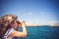 看通过双筒望远镜的水手孩子 库存照片
