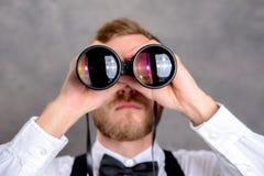 看通过双筒望远镜的年轻有胡子的人 库存图片