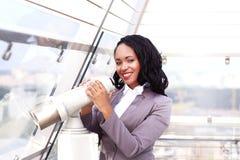 看通过双筒望远镜都市风景的一名愉快的女实业家的画象 库存图片