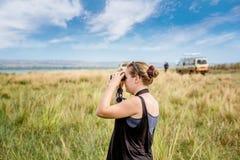 看通过在一个徒步旅行队的双筒望远镜的妇女在非洲 库存图片