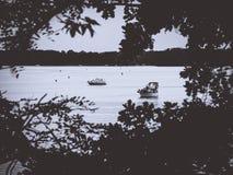 看通过在一个镇静湖的一个叶子孔有小船的 免版税图库摄影