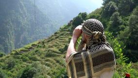 看通过在一串迁徙的足迹的双筒望远镜的徒步旅行者对安纳布尔纳峰营地,喜马拉雅山,尼泊尔 股票录像