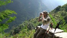 看通过在一串迁徙的足迹的双筒望远镜的徒步旅行者对安纳布尔纳峰营地,喜马拉雅山,尼泊尔 股票视频