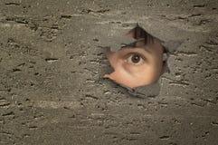 看通过在墙壁的一个孔的眼睛。 免版税图库摄影