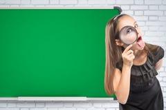 看通过在学校书桌背景的一个放大镜的逗人喜爱的小女孩 培训的概念 免版税库存照片