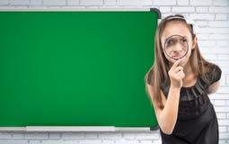 看通过在学校书桌背景的一个放大镜的逗人喜爱的小女孩 培训的概念 库存照片