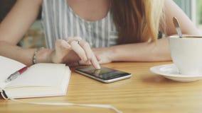 看通过在智能手机的图片的妇女在咖啡馆 库存照片