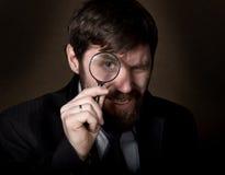 看通过在棕色背景的放大镜的英俊的年轻商人画象  库存图片