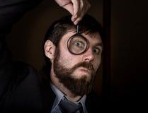 看通过在棕色背景的放大镜的英俊的年轻商人画象  免版税库存照片