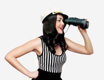 看通过在白色的双筒望远镜的美丽的微笑的年轻深色的妇女水手 免版税图库摄影