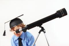 看通过在白色背景的一台望远镜的学术帽子的小男孩 库存图片