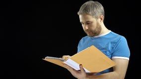 看通过在黄色文件夹的纸的蓝色T恤杉的英俊的人 Cotract,票据,清单概念 投反对票 股票录像