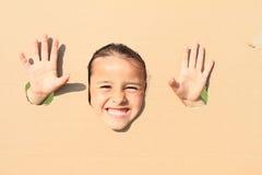 看通过孔的咧嘴笑的女孩 免版税图库摄影