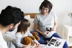 看通过家庭照片册页的怀孕的家庭 免版税库存图片