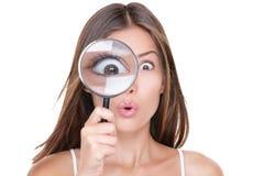 看通过放大镜的滑稽的妇女 免版税库存照片