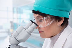 看通过显微镜的生物学家 免版税图库摄影