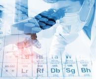 看通过显微镜的科学家为化学测试样品,审查 图库摄影