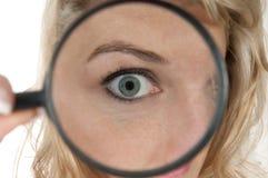 看通过有大眼睛的一个放大镜的妇女 图库摄影