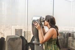 看通过硬币观察者的妇女看中央公园, M 免版税库存照片
