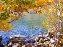 看通过秋天金黄叶子清楚的山湖 库存图片