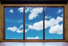 看通过窗口、木窗架与蓝天和白色云彩视图 库存照片