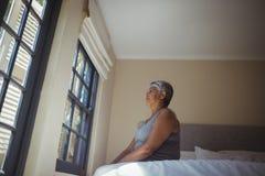 看通过窗口的体贴的资深妇女在床屋子里 库存照片