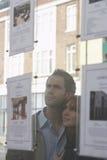 看通过窗口的夫妇房地产经纪商 免版税库存照片