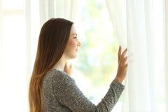 看通过窗口的沉思妇女 免版税库存照片