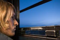 看通过窗口的年轻人 图库摄影