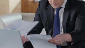 看通过纸和键入在膝上型计算机,统计报告的商人 影视素材