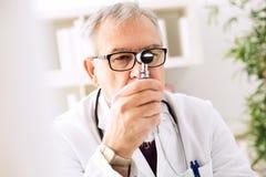 看通过耳镜的耳鼻喉科医师 免版税库存照片