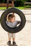看通过轮胎摇摆的男孩 免版税库存图片
