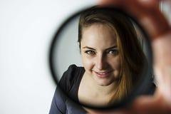 看通过镜头和微笑的年轻女人 摄影工具和设备 图库摄影